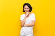 Leinwandbild Motiv Asian young woman over isolated yellow wall with glasses and smiling