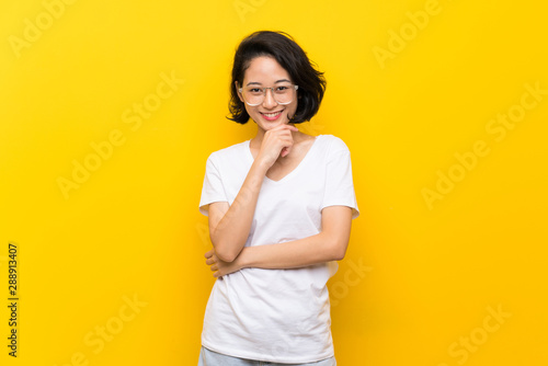Asian young woman over isolated yellow wall with glasses and smiling