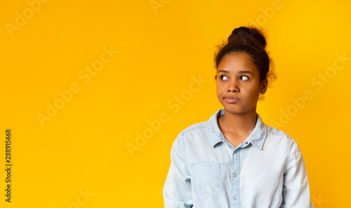 Annoyed african girl looking aside at free space Canvas Print