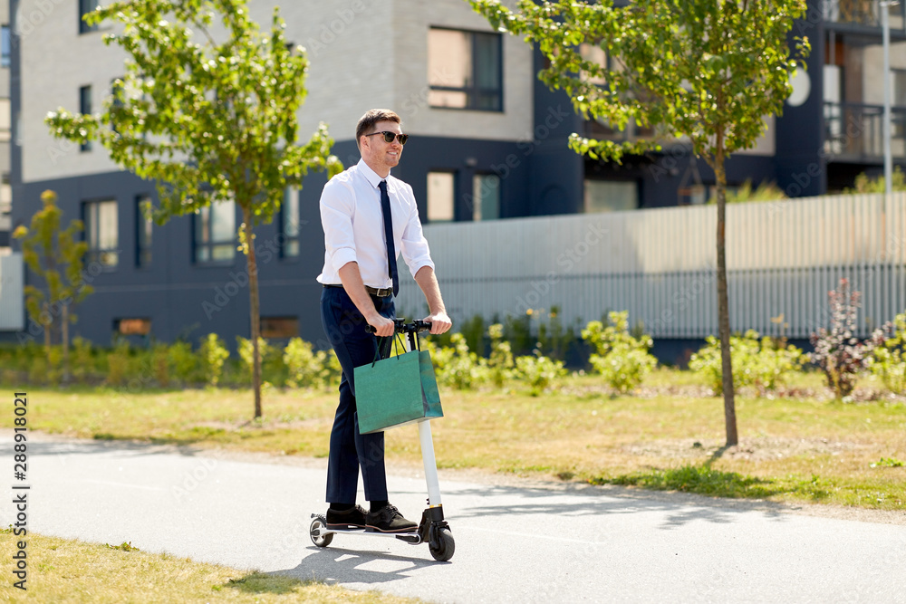 Fototapeta business and people and concept - young businessman with shopping bag riding electric scooter outdoors