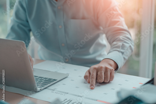 Obraz Business Man with laptop, Calendar in office, Business management event . Organizational management, business plan targeted marketing activities, media relations advertising. - fototapety do salonu