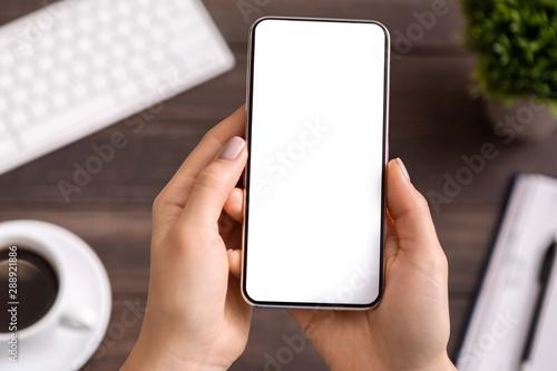 Fotografía  Woman demonstrating modern smartphone with blank white screen