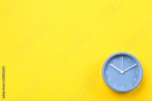 Obraz Blue round clock on yellow background - fototapety do salonu