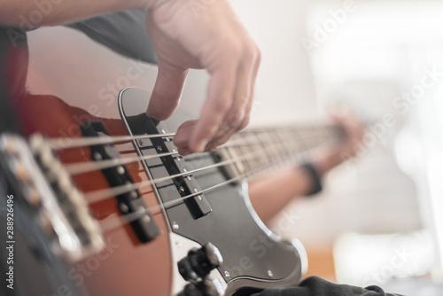 A man plays a bass guitar close-up. Toned photo. - 288926496