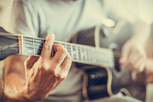 A man plays the guitar close-up. Toned photo. - 288926603