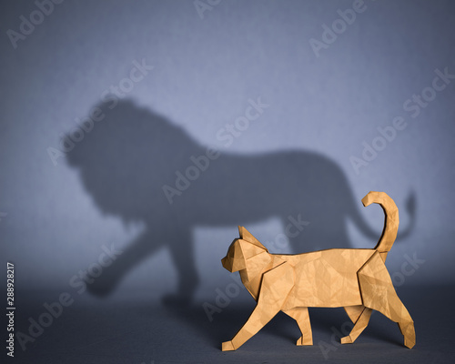 Obraz Concept of hidden potential. A paper figure of a cat that fills the shadow of a lion. 3D illustration - fototapety do salonu