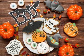 Halloween gingerbread cookies with candies in plate on brown wooden table