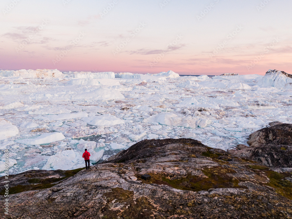 Fototapeta Travel in arctic landscape nature with icebergs - Greenland tourist man explorer - tourist person looking at amazing view of Greenland icefjord - aerial drone image. Man by ice and iceberg, Ilulissat.