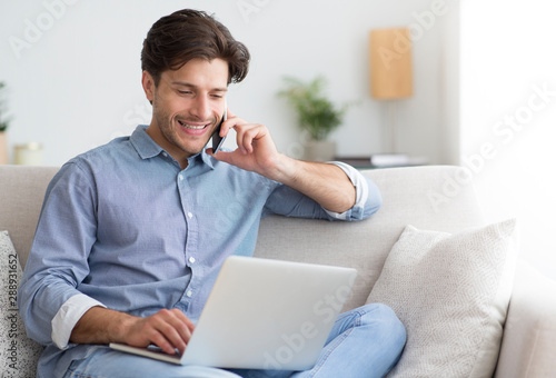 Young entrepreneur talking on cellphone working at laptop at home
