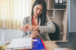 Leinwandbild Motiv Professional Business woman seeing wrist watch to check time at office.Asian Businesswoman look at clock to work.On desk with glasses,laptop,book,annual and summary report.Time out for appointment mee