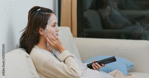 Fototapety, obrazy: Woman apply paper mask on face and watch tv at home