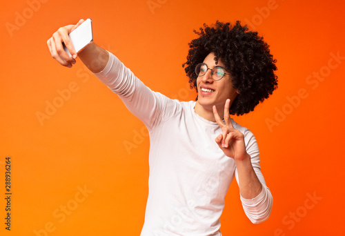 Young black guy making selfie with peace gesture on cellphone