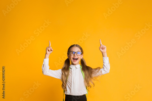 Fotomural  Excited School Girl Pointing Fingers Up Over Yellow Background, Copyspace