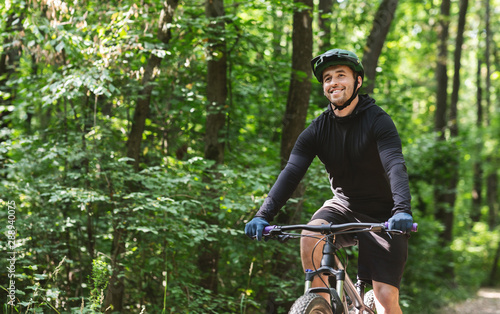 Photo Cheerful sportsman enjoying cycling down forest path