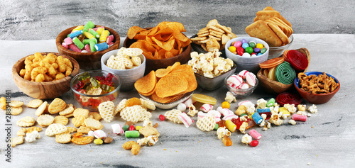 Salty snacks. Pretzels, chips, crackers and candy sweets on table Lerretsbilde
