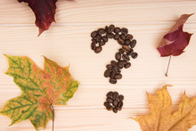 Question Mark. A Question Mark Collected From Roasted Coffee Beans Lies On A Wooden Tabletop. Nearby Are Several Maple Autumn Leaves.