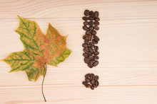 Exclamation Mark. An Exclamation Mark Collected From Roasted Coffee Beans Lies On A Wooden Tabletop. Nearby Lies A Maple Autumn Leaf