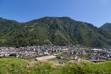 Fototapeta na wymiar panoramic of small town surrounded by mountains - landscape of latino america Guatemala