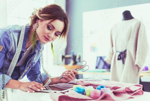 Fototapeta Fashion designer woman working with ipad on her designs in the studio