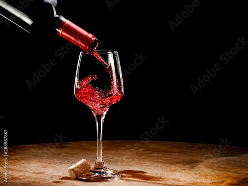 Obraz na plátně  Red wine pouring in glass on a old wooden table in dark winery