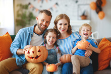 Happy  Family Mother Father And Children Prepare For Halloween Decorate  Home With Pumpkins,  Laughing And  Play