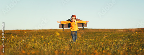 Fototapety, obrazy: Child pilot aviator with wings of airplane dreams of traveling in summer  at sunset.