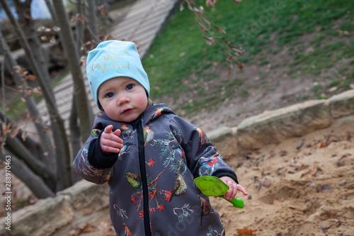 Kind Hannah beim unbeschwerten Spielen in einem Sandkasten Wallpaper Mural