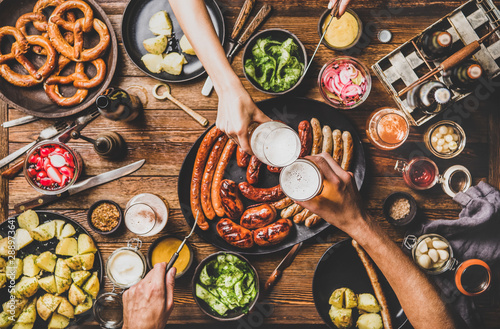 Flat-lay of Oktoberfest dinner table with grilled meat sausages, pretzel pastry, potatoes, cucumber salad, sauces, beers and peoples hands clinking glasses over dark wooden background, top view - 288973641