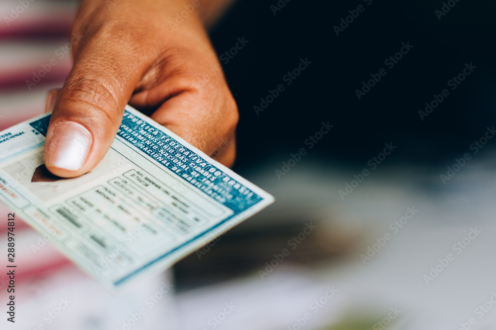 Fototapeta Man holds National Driver's License (CNH). Official document of Brazil, which attests the ability of a citizen to drive land vehicles.