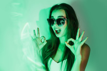 Night Portrait Of A Young Excited Girl With Reflection In Sunglasses In Green Neon Light, Showing Ok Sign With Both Hands.