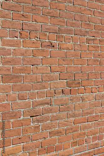 Old grungy red clay brick wall texture in common bond pattern, with deteriorating surface (angle view)