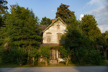 A Formerly Grand Victorian-era House Sits Abandoned And Partly Overgrown By Trees.