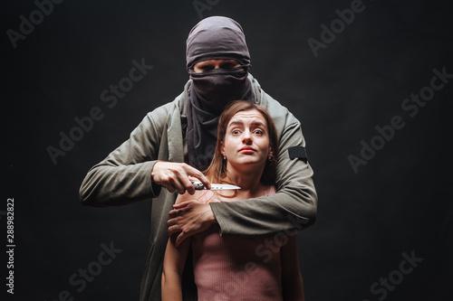 Fototapeta  Masked man threatening girl with knife