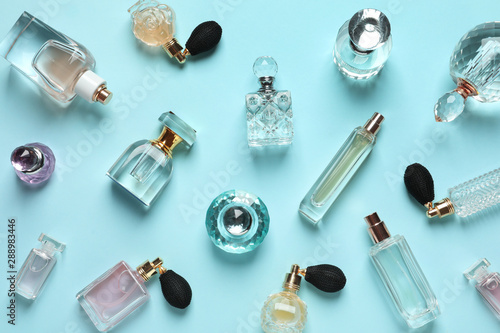 Fototapeta Flat lay composition with different perfume bottles on light blue background obraz