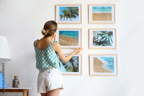Fototapeta Female interior designer decorating white wall with pictures indoors obraz