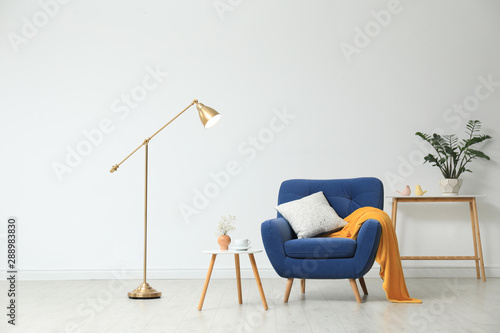 Obraz Stylish living room interior with comfortable furniture near white wall - fototapety do salonu