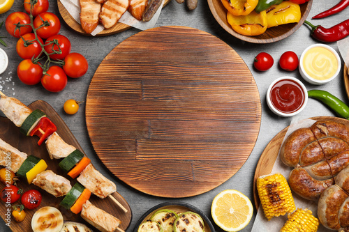 Fototapeta Flat lay composition with barbecued meat and vegetables on grey table. Space for text obraz