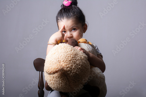 Foto  Close up of Little girl portrait holding a fat dog doll in hands