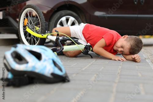 Little boy fallen from bicycle after car accident and helmet on road Canvas Print