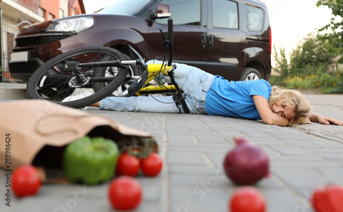 fototapeta na drzwi i meble Woman fallen from bicycle after car accident and scattered vegetables on street