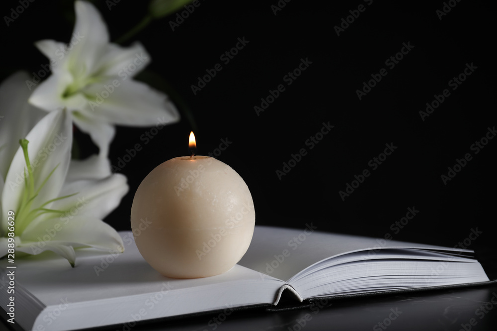 Fototapeta Burning candle, book and white lilies on table in darkness, closeup with space for text. Funeral symbol