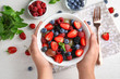 Woman holding bowl with fresh tasty fruit salad over white wooden table, top view