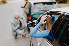 Senior Man And Young Woman Arguing After Car Crash.