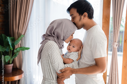 muslim parent kissing together with baby boy at home Fotobehang