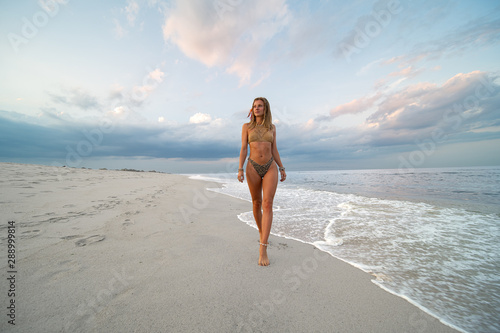 Beautiful tanned woman in swimsuit is walking on tropical beach