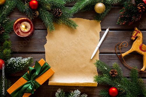 Fototapeta Letter to Santa Claus concept. Paper on dark wooden background with New Year decoration top view mockup copy space obraz