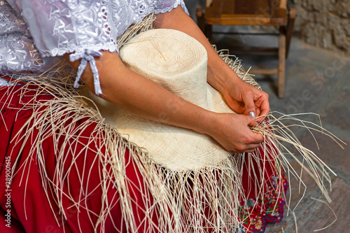 Fotografía  Woman weaving a Panama hat, also known as the traditional brimmed straw hat made of the Toquilla palm, which is on the Unesco Intangible Cultural list and famous from the city of Cuenca, Ecuador