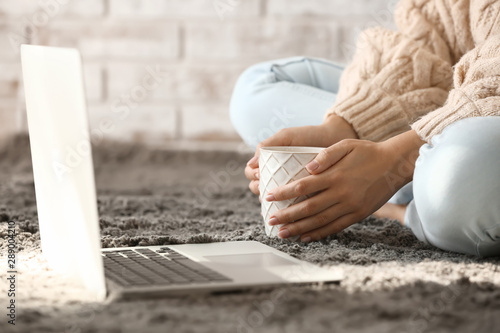 Obraz Young woman with laptop drinking hot tea at home - fototapety do salonu