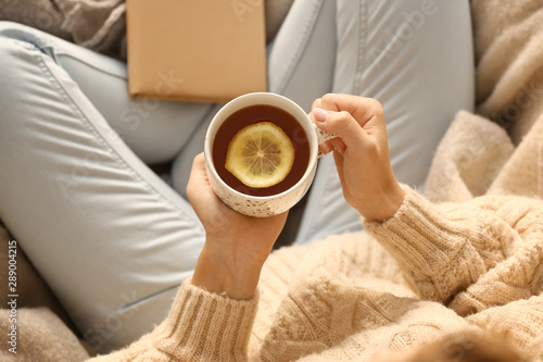 In de dag Thee Young woman drinking hot tea at home