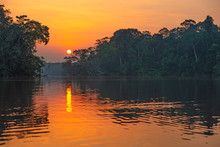 Reflection Of A Sunset By A Lagoon Inside The Amazon Rainforest Basin. The Amazon River Basin Comprises The Countries Of Brazil, Bolivia, Colombia, Ecuador, Guyana, Suriname, Peru And Venezuela.